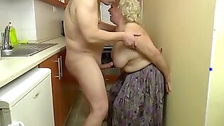 Insatiable, blonde granny is playing with her tits and her lovers dick, in the kitchen
